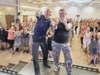 Chris MacDonald og regionsformand for Danske Fysioterapeuter, Lise Jensen, foran en flok glade fysioterapeuter til fejringen af  100 år med fysioterapi i Danmark. Foto: Anders Heegaard.