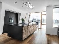 Højskabe er indbygget i en niche mellem de to skrå vægge – en spændende og skæv detalje. De sorte elementer i egefinér fra Tvis Køkkeners Unika-serie spiller sammen med det sorte i køkkenborde, lamper og reoler. PR-foto: Tvis Køkkener.